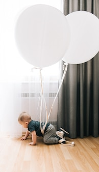 Schattige kleine jongen kruipen met grote witte ballonnen, gelukkige jeugd, spelletjes voor kinderen