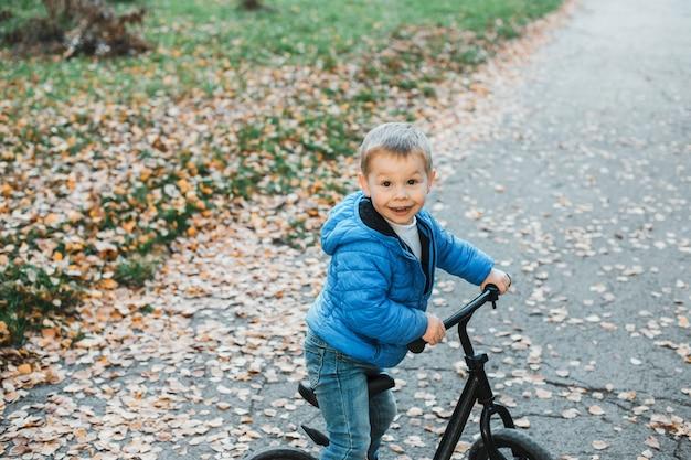 Schattige kleine jongen lachend tijdens het fietsen buiten.