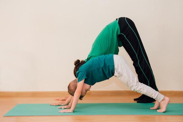 Schattige kleine jongen leert yoga te doen in de sportschool