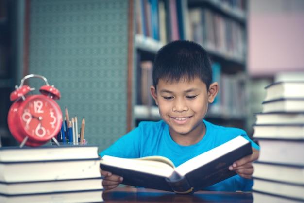 Schattige kleine jongen leesboek in de bibliotheek