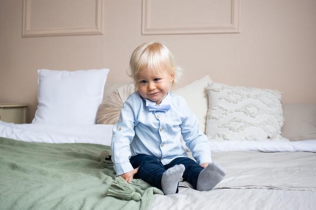 Schattige kleine jongen liggend op bed. mensen, kinderen, rust en comfortconcept.