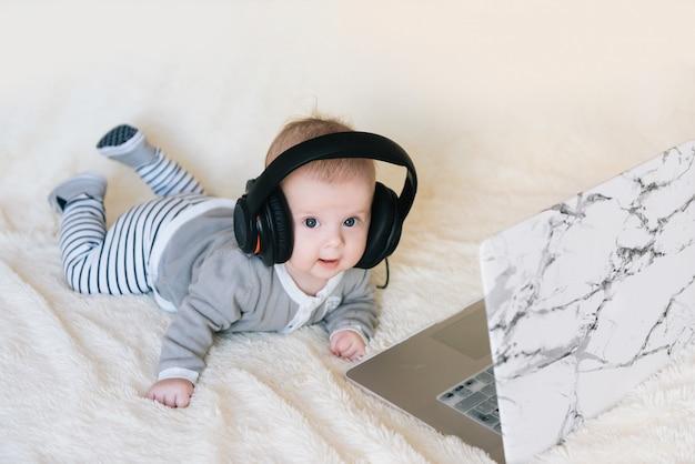 Schattige kleine jongen ligt in de koptelefoon en kijkt in de laptop