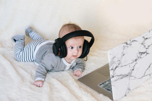 Schattige kleine jongen ligt op zijn buik in hoofdtelefoons en kijkt in de laptop