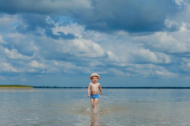 Schattige kleine jongen loopt door het water op het strand