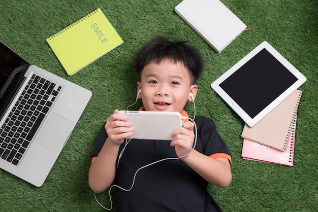 Schattige kleine jongen luistert naar muziek op het gras met zijn laptop, tablet en notebooks in de buurt.