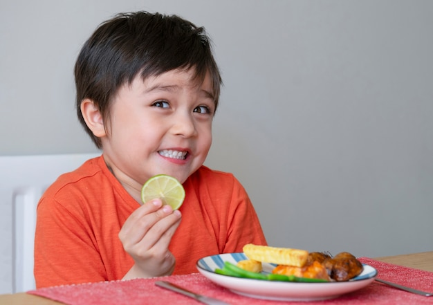 Schattige kleine jongen maakt grappig gezicht na het proeven van een zure citroen