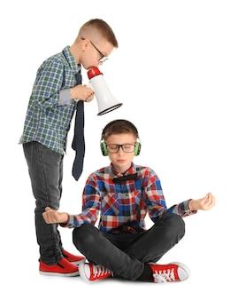 Schattige kleine jongen mediteren en negeren van zijn vriend met megafoon, op wit
