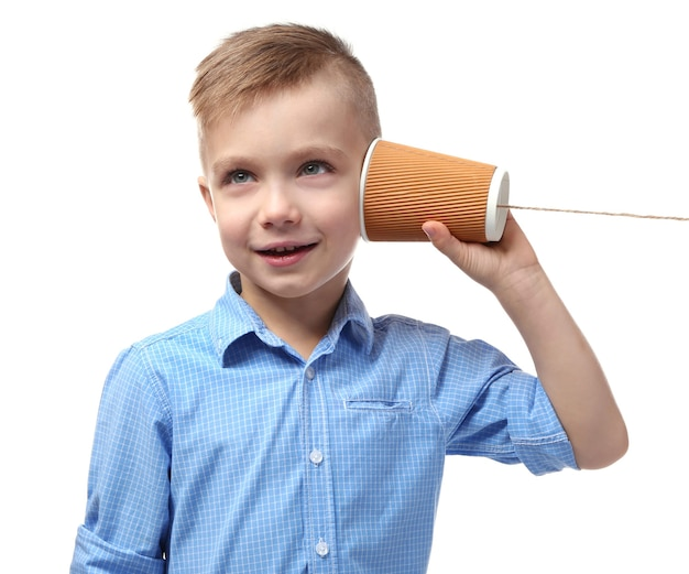 Schattige kleine jongen met behulp van plastic beker als telefoon, op witte muur