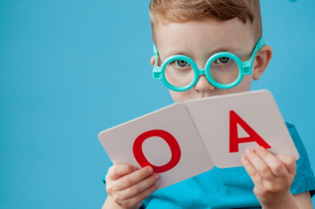 Schattige kleine jongen met brief op achtergrond. kind leren letters.