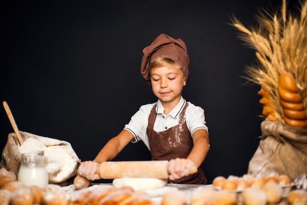 Schattige kleine jongen met chef-kok hoed koken