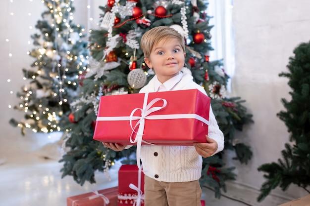 Schattige kleine jongen met de doos van de gift van kerstmis in de buurt van kerstbomen met verlichting. prettige kerstdagen en fijne feestdagen