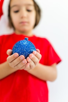 Schattige kleine jongen met decoratie bal dragen kerstmuts en glimlachen