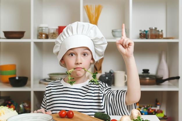 Schattige kleine jongen met een koksmuts die met de hand naar boven wijst. koken voedsel concept. chef-kok heeft een geweldig idee