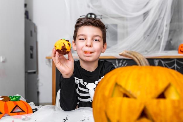 Schattige kleine jongen met eng kostuum genieten van zijn halloween cupcakes. jack o 'lantern halloween-pompoen op tafel en andere enge decoraties