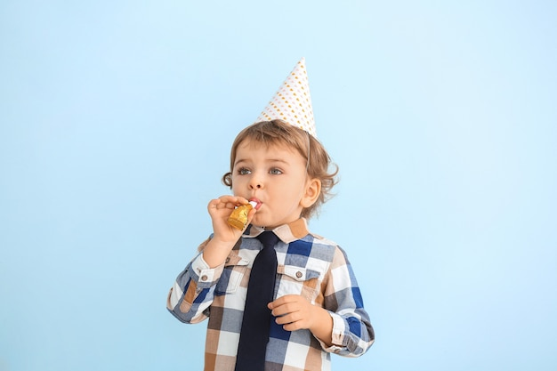 Schattige kleine jongen met feest decor op kleur