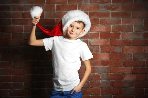 Schattige kleine jongen met geschenkdoos op bakstenen muur achtergrond.