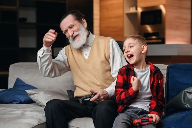 Schattige kleine jongen met grootvader zittend op de bank en het spelen van videospel met gamepad