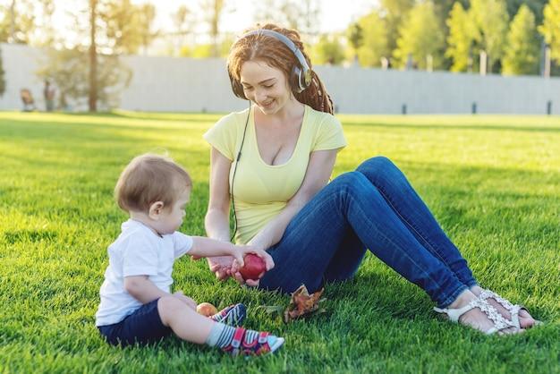 Schattige kleine jongen met haar moeder spelen met appels