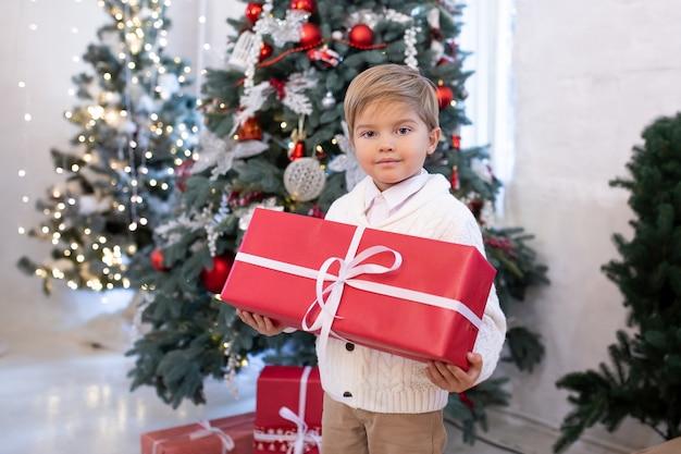 Schattige kleine jongen met kerstcadeau geschenkdoos in de buurt van kerstbomen met verlichting