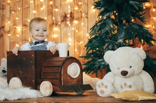 Schattige kleine jongen met kerstverlichting en decoraties