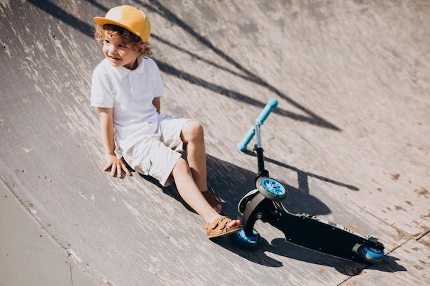 Schattige kleine jongen met krullend haar rijden scooter