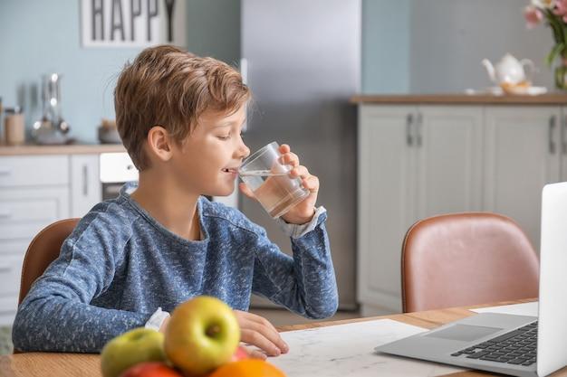 Schattige kleine jongen met laptop drinkwater thuis