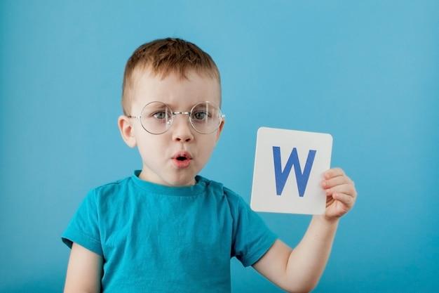 Schattige kleine jongen met letter. kind leert brieven. alfabet