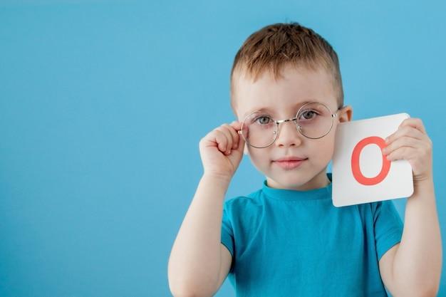 Schattige kleine jongen met letter op blauwe muur. kind dat brieven leert. alfabet