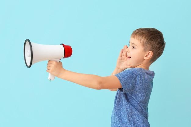 Schattige kleine jongen met megafoon op kleur