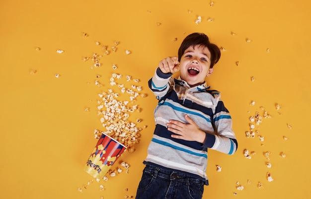 Schattige kleine jongen met popcorn liggend op de gele vloer.