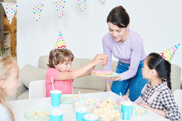 Schattige kleine jongen met smakelijke roze geglazuurde donut aangeboden door jonge vrouw tijdens verjaardagsfeestje thuis
