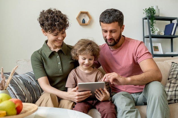 Schattige kleine jongen met touchpad en zijn jonge aanhankelijke ouders kijken naar online video of film of op zoek naar nieuwsgierige cartoons in het net