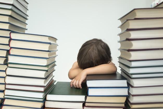 Schattige kleine jongen met veel boeken