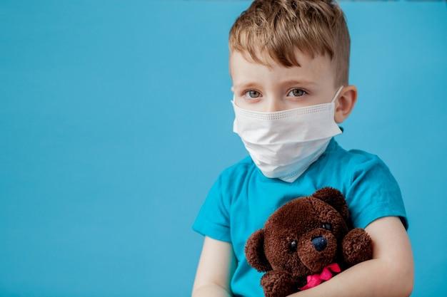 Schattige kleine jongen met vernevelaar op blauwe achtergrond. allergie concept.