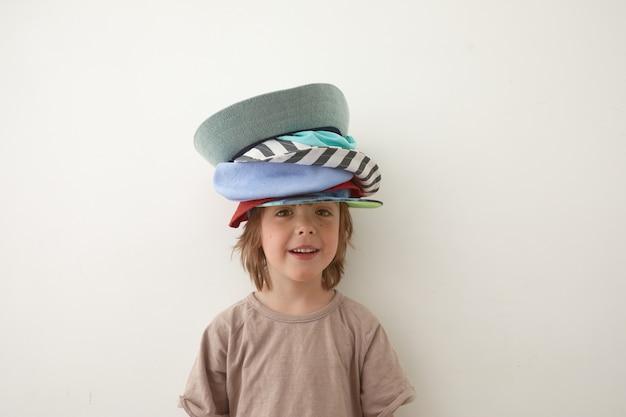 Schattige kleine jongen met verschillende hoeden op het hoofd