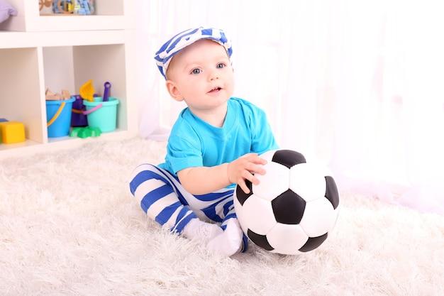 Schattige kleine jongen met voetbal in de kamer
