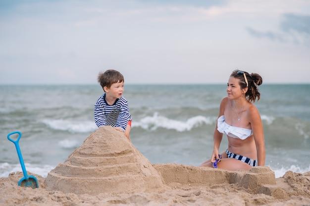 Schattige kleine jongen met zijn moeder spelen aan de kust