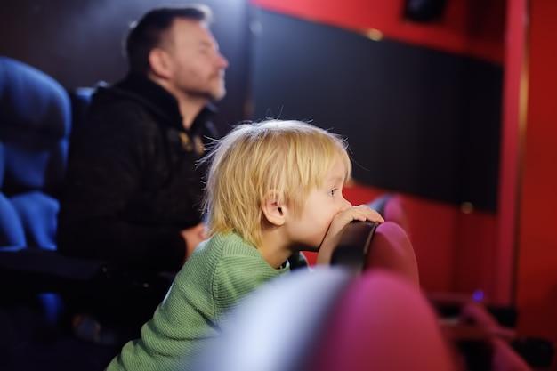Schattige kleine jongen met zijn vader kijken cartoon film in de bioscoop