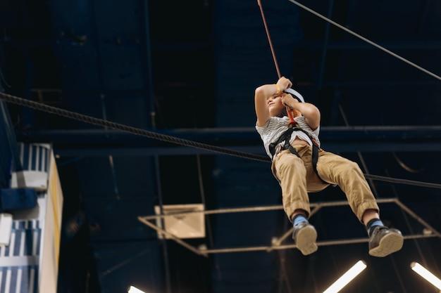 Schattige kleine jongen naar beneden op zipline in avonturenpark langs hindernisbaan. hoog touwpark binnenshuis. hoge kwaliteit foto