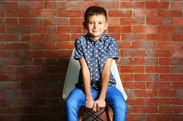 Schattige kleine jongen op bakstenen muur achtergrond. kindermode concept