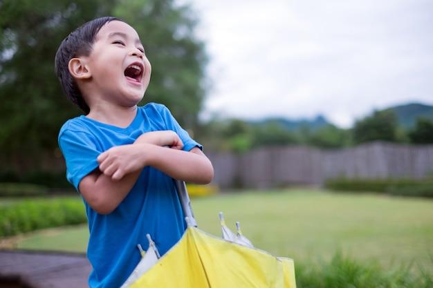 Schattige kleine jongen permanent en leuke gele paraplu met outdoor achtergrond