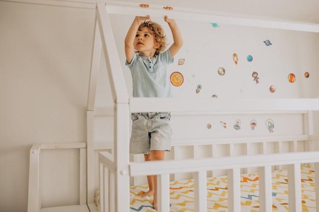Schattige kleine jongen plezier in bed in de vorm van een huis