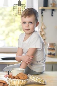 Schattige kleine jongen portret in een witte t-shirt zittend op houten tafel ontbijt in keuken kamer