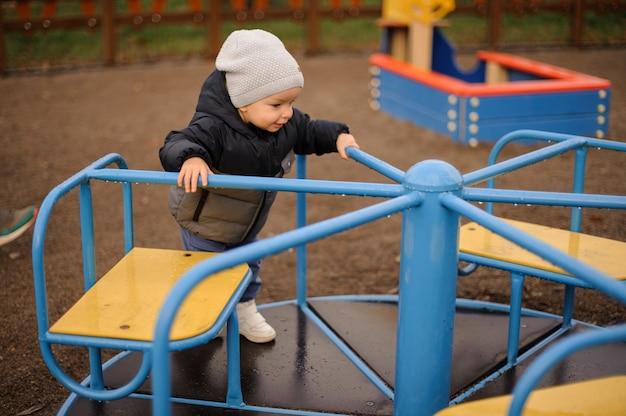 Schattige kleine jongen rijden op de carrousel