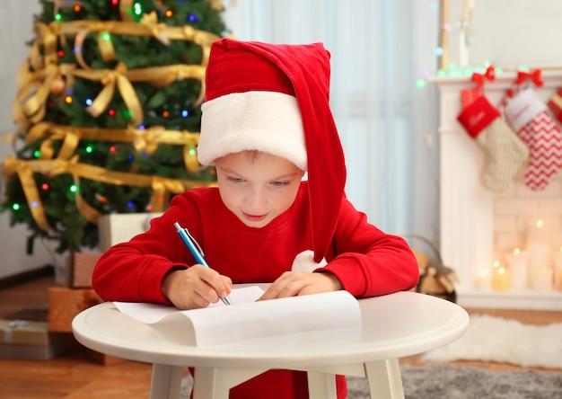 Schattige kleine jongen schrijven brief aan de kerstman aan tafel