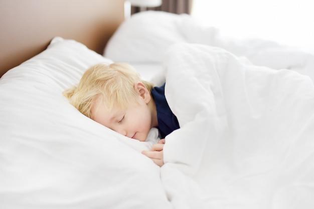 Schattige kleine jongen slaapt. vermoeid kind dat een dutje in het bed van de ouder neemt.
