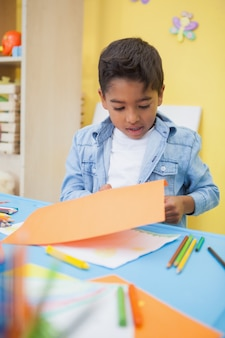 Schattige kleine jongen snijden papier vormen in de klas
