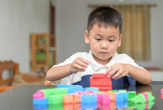 Schattige kleine jongen speelt hout baksteen