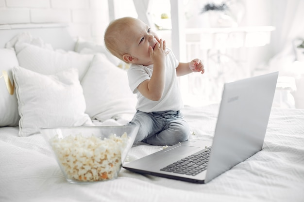 Schattige kleine jongen speelt met een laptop op een bed