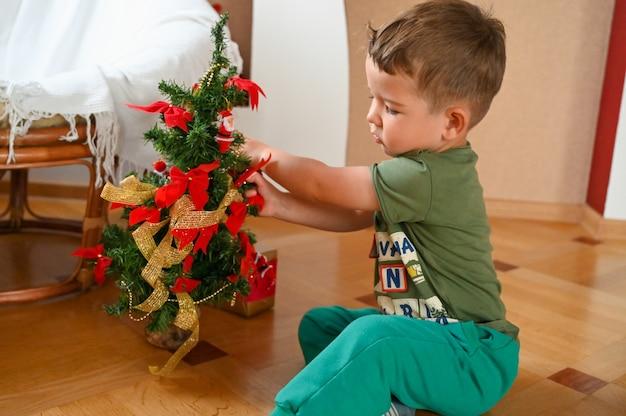 Schattige kleine jongen speelt met een miniatuur kerstboom